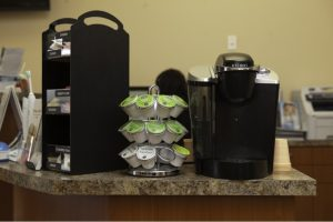 A keurig coffee machine on a counter next to coffee pods