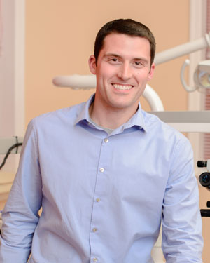 A male doctor smiling in front of dental technology